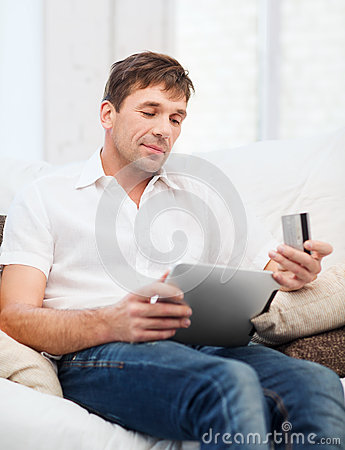 Man with tablet pc and credit card at home