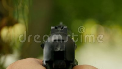 Man takes aim and shoots. Hand with a gun,  man takes aim and shoots rear view stock video footage