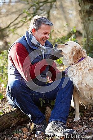 Man Taking Dog On Walk Through Autumn Woods