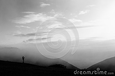 A man taking photos on a mountain peak, with fog and mist all ar Stock Photo