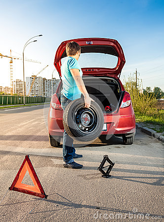 Free Man Taking Spare Wheel Out Of Trunk Royalty Free Stock Images - 40246269