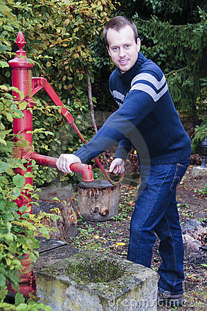 Man taking water from water well