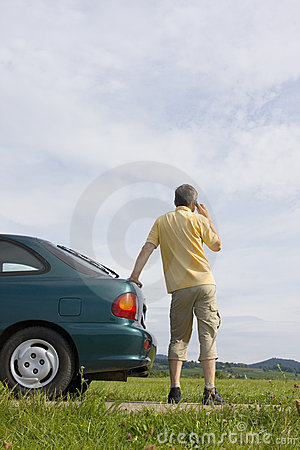 Man talking on cell phone beside his car
