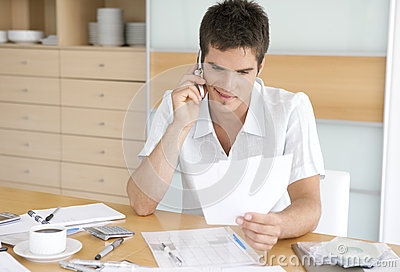 Man Talking on Cell Working on Finances