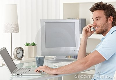 Man talking on phone using computer