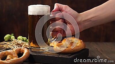 Man tar ett glas lätt öl från ett mörkt träbord. lager videofilmer
