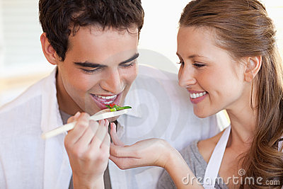 Man is tasting the meal his girlfriend is cooking