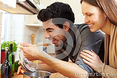 Man tasting soup in kitchen