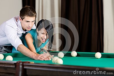 Man teaching girl to play billiard
