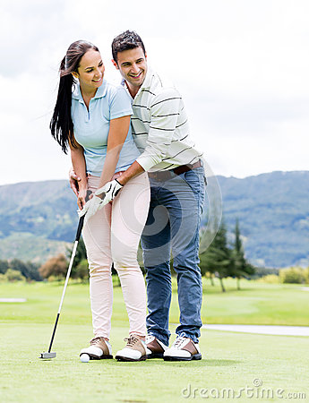Man teaching woman to play golf