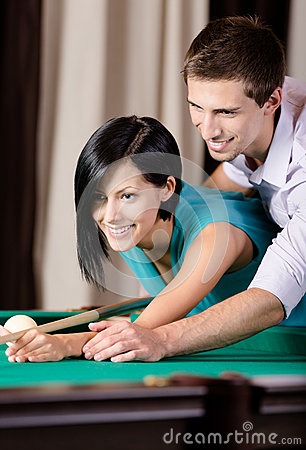 Man teaching young woman to play billiards