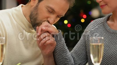 Man tenderly kissing woman hand, romantic date on Christmas night, closeup. Stock footage stock footage