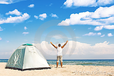 Man with tent enjoying camping on beach