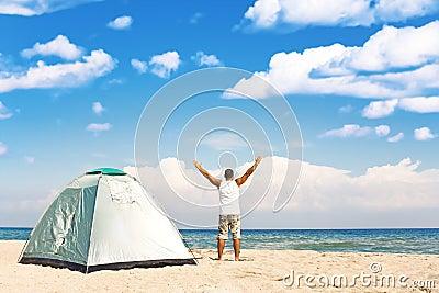 Man with tent enjoying camping on beach