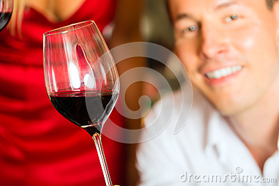 Man testing wine in background barrels