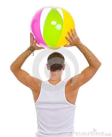 Man throwing beach ball. Rear view