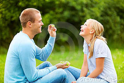 Man throwing a grape in his girlfriend s mouth