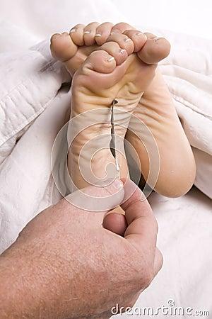 Man tickling womans feet