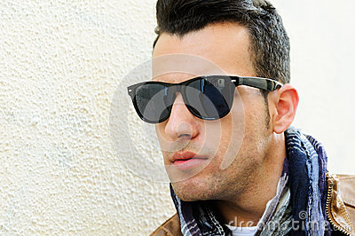 Man with tinted sunglasses in urban background