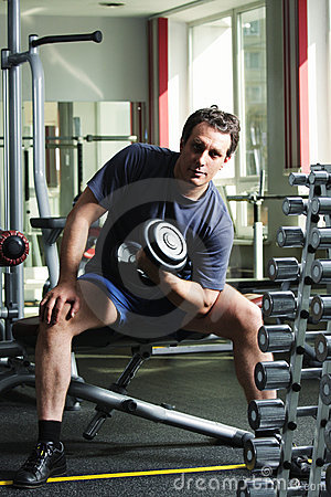 Man training biceps with dumb-bell