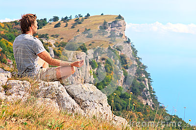 Man Traveler Relaxing Yoga Meditation sitting on stones with Rocky Mountains and blue sky on Background