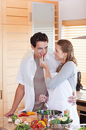 Man trying the meal his girlfriend is preparing