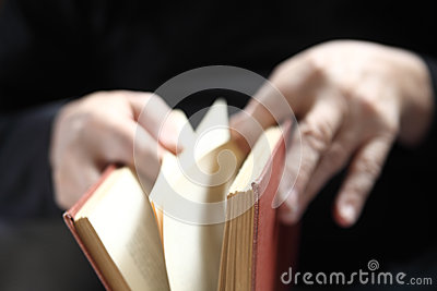 Man turns pages of book