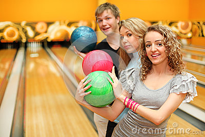 Man and two girls made row of balls in bowling
