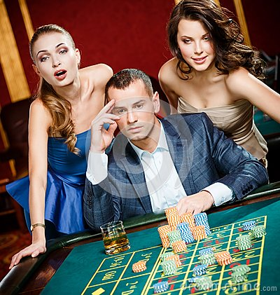 Man with two girls playing roulette at the casino