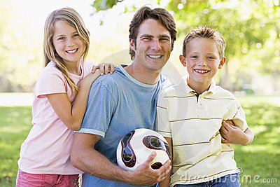 Man and two young children holding volleyball