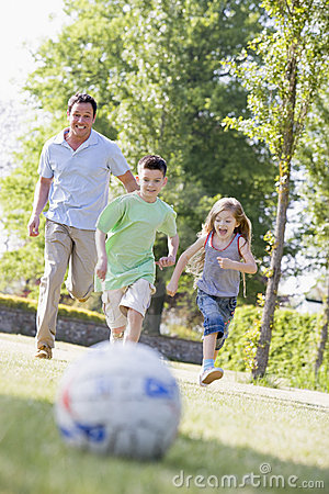 Man and two young children outdoors playing soccer
