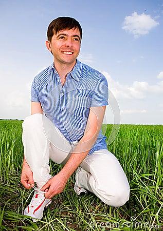 Man is Tying Laces In A Green Field