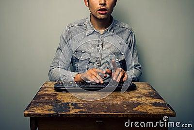 Man typing on keyboard at old desk