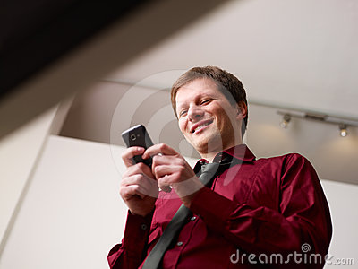 Man typing sms on smartphone and smiling