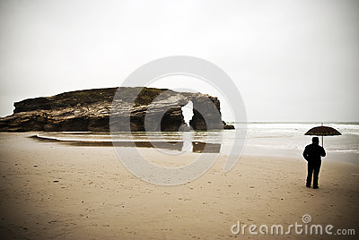 Man with umbrella on the beach.