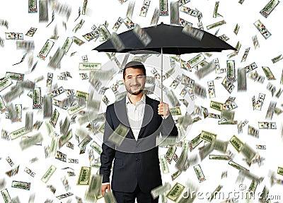 Man with umbrella standing under money rain
