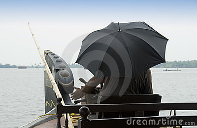 Man with umbrella steers a Houseboat