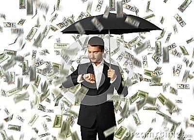 Man under money rain looking at watch