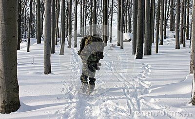 A Man in the Uniform Walking Through Winter Forest