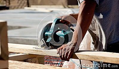 Man using circular saw on wood