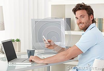 Man using computer and phone at home