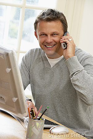 Man Using Computer And Talking On Phone