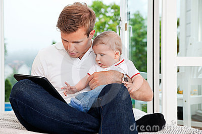 Man Using Digital Tablet while Holding Child