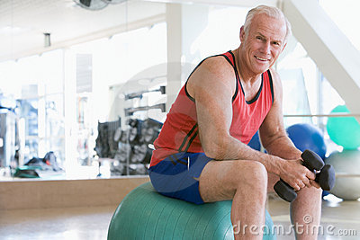 Man Using Hand Weights On Swiss Ball At Gym