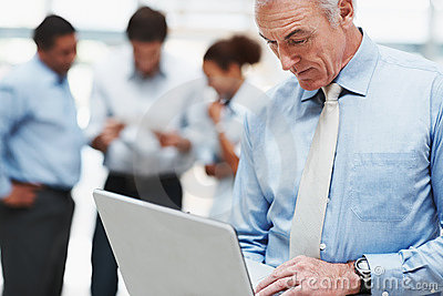 Man using laptop with coworkers at the back