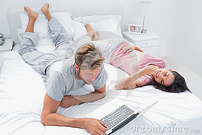 Man using a laptop next to his wife lying on bed