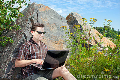 Man using a laptop in summer day