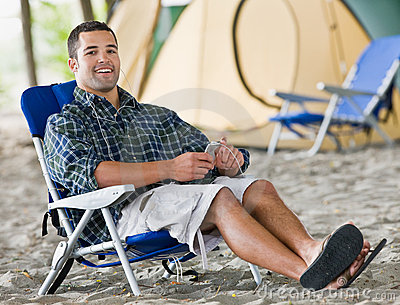 Man using mp3 player at campsite