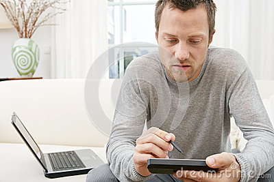 Man using tablet and computer on sofa at home.
