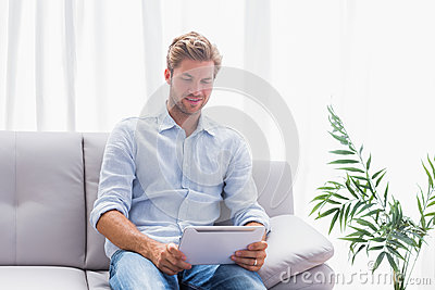 Man using a tablet while he is sat on the couch